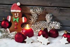 Christmas gingerbread bear christmas bulbs cinnnamon stars pine twig candle on pile of snow against wooden wall Royalty Free Stock Photos