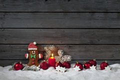 Christmas gingerbread bear christmas bulbs cinnnamon stars pine twig candle on pile of snow against wooden wall Royalty Free Stock Images