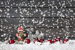 Christmas gingerbread bear christmas bulbs cinnnamon stars pine twig on pile of snow against wooden wall snow is falling Stock Images