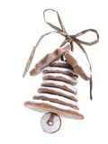 Christmas gingerbread bell. Christmas bell assembled from gingerbread shaped cookies and tied with golden ribbon shot over white blue background Royalty Free Stock Image