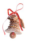 Christmas gingerbread bell. Christmas bell assembled from gingerbread shaped cookies and tied with red ribbon shot over white blue background Stock Images