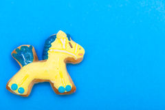 Christmas gingerbread cake pony with icing and decoration on blue. Homemade gingerbread cake pony with icing and blue yellow decoration on blue. Christmas and royalty free stock photography