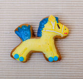 Christmas gingerbread cake pony with icing and decoration on brown. Homemade gingerbread cake pony with icing and blue yellow decoration on brown as christmas royalty free stock photos