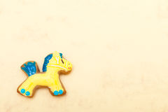 Christmas gingerbread cake pony with icing and decoration on brown. Homemade gingerbread cake pony with icing and blue yellow decoration on brown paper stock images