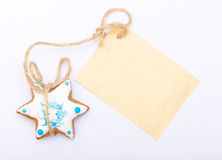 Christmas gingerbread cake star with icing and decoration and blank card Royalty Free Stock Photo