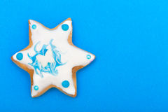 Christmas gingerbread cake star with icing and decoration on blue Stock Images