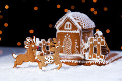 Christmas gingerbread cookie house and deers. Holidays food setting Royalty Free Stock Images
