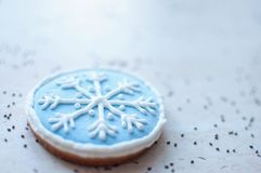 A Christmas gingerbread cookie in the shape of a blue round snowflake close-up. Selective focus, bokeh. A Christmas gingerbread cookie in the shape of a blue stock image