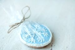 A Christmas gingerbread cookie in the shape of a blue round snowflake close-up. Selective focus, bokeh. A Christmas gingerbread cookie in the shape of a blue stock photography