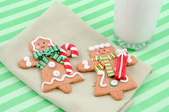Christmas gingerbread cookies. Set of man and woman christmas gingerbread cookies on a napkin, with tall glass of cold milk Royalty Free Stock Photography