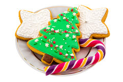 Christmas ornate Gingerbread cookies and candy cane on a white plate Royalty Free Stock Photography