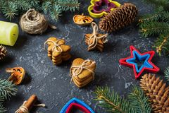Christmas gingerbread cookies and fir tree and cones on dark stone background. Royalty Free Stock Photography