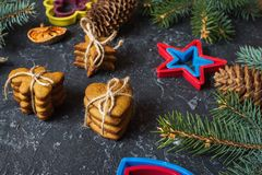 Christmas gingerbread cookies and fir tree and cones on dark stone background. Royalty Free Stock Image