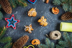 Christmas gingerbread cookies and fir tree and cones on dark stone background. Royalty Free Stock Photo