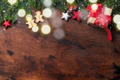 Christmas gingerbread cookies, gift box and xmas fir tree branch over wooden backdrop. Top view with space for your greetings royalty free stock photography