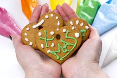 Christmas gingerbread cookies in hand with colored sweet icing. gingerbread cookies with green text Xmas