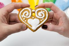 Christmas gingerbread cookies in hand with colored sweet icing. gingerbread cookies with white drawing