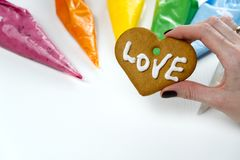 Christmas gingerbread cookies in hand with colored sweet icing. gingerbread cookies with white text Love