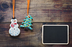Christmas gingerbread cookies hanging over wooden background Stock Image