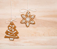 Christmas Gingerbread Cookies. Gingerbread cookies hanging by twine over a wooden background royalty free stock image