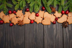 Christmas Gingerbread Cookies. Holiday concept decorated with Fir branches and Cranberries. Royalty Free Stock Photo