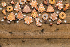 Christmas gingerbread cookies, nuts and snowflakes on wooden background with space for your text Royalty Free Stock Photo