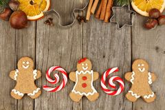 Christmas gingerbread cookies, peppermints and baking goods on rustic wood Royalty Free Stock Photos
