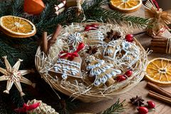 Christmas gingerbread cookies in a round wicker basket. Decorated Christmas gingerbread cookies in a round wicker basket on a wooden table stock photography