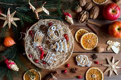 Christmas gingerbread cookies in a round wicker basket on a wood. Decorated Christmas gingerbread cookies in a round wicker basket, with spruce branches, straw stock images