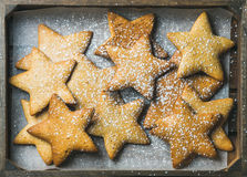 Christmas gingerbread cookies in shape of stars with sugar powder. Sweet Christmas holiday gingerbread cookies in shape of stars with sugar powder on baking Stock Images