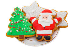Christmas Gingerbread colored cookies in the shape of  stars, Santa Claus, Christmas tree on a white plate Stock Photo
