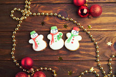Christmas gingerbread cookies on wooden background. Christmas gingerbread cookies with three snowmans on wooden background with Christmas balls. Top view Royalty Free Stock Images