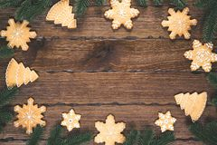 Christmas gingerbread, fir branches in the form of a frame on wooden brown background. Christmas composition. royalty free stock photo