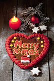 Christmas gingerbread heart with candle cinnamon stars pine twig christmas bulb on wooden floor Stock Image