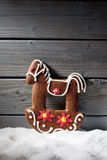 Christmas gingerbread horse on heap of snow against wooden background Royalty Free Stock Photos