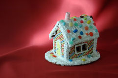 Christmas Gingerbread house. On a festive red canvas, light-painted from behind Stock Images