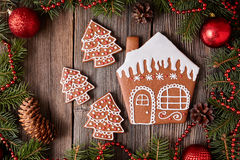 Christmas gingerbread house and fur tree cookies. Composition with xmas decorations on vintage wooden table background. Homemade traditional dessert food recipe Stock Image