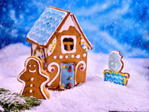 Christmas gingerbread house in snow on blue background. Royalty Free Stock Photography