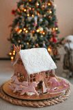 Christmas gingerbread house with unicorns. Christmas gingerbread house with unicorn cookies in pink icing and decorated with confection balls and coconut chips royalty free stock photography