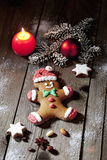 Christmas gingerbread man with candle cinnamon star nuts pine twig christmas bulb on wooden floor Royalty Free Stock Photography