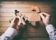 Christmas gingerbread man cookie and prise tag. Young woman hands holding christmas gingerbread man cookie and prise tag on wooden background, Photo in old color stock images