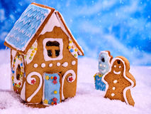 Christmas gingerbread man and house in snow on blue background. Royalty Free Stock Photography