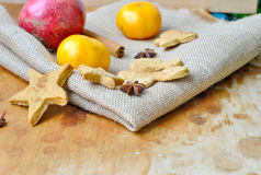 Christmas gingerbread man and a star anise and tangerines. On a napkin from a rough fabric Royalty Free Stock Photography