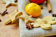 Christmas gingerbread man and a star anise and tangerines. On a napkin from a rough fabric Royalty Free Stock Image