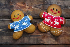 Christmas gingerbread men on wooden background. Smiling christmas gingerbread men on wooden background Royalty Free Stock Photo