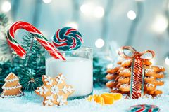 Christmas gingerbread and milk with decorations, snow, christmas tree branches on bokeh blurred lights background. Free space Royalty Free Stock Photo