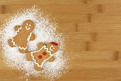 Christmas gingerbread people with powdered sugar on wood Stock Photography