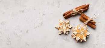Christmas gingerbread snowflakes cookies on grey background. Christmas gingerbread snowflakes cookies and cinnamon sticks on grey background with copy space stock photos