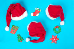 Christmas gingerbreads and Santa Claus`s caps lie on a blue back Royalty Free Stock Photography