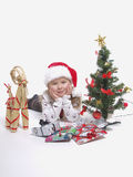 Christmas girl. Happy girl with christmas gifts next to the tree in studio Stock Images